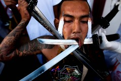 A devotee of the Chinese shrine of Kathu Shrine pierces his cheeks with swords during a procession on October 4. (Athit Perawongmetha/Getty Images)