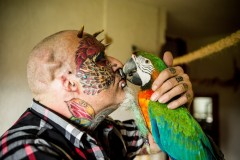 "Ted Richards, 56, from Hartcliffe in Bristol, who has had his ears taken off so he can look more like his Parrot. August 16 2015.A man who had his face and eyeballs tattooed to look like his pet parrots has gone a step further - by cutting off his EARS. Bonkers Ted Richards, 56, is obsessed by pets Ellie, Teaka, Timneh, Jake and Bubi and has his face tattooed with colourful feathers. But the animal nut - who has 110 tattoos, 50 piercings and a split tongue - has now had both his ears removed by a surgeon in a six hour operation. Eccentric Ted has given his severed ears to a friend who ""will appreciate them"" and is now planning to find a surgeon prepared to turn his nose into a BEAK. Photo by  