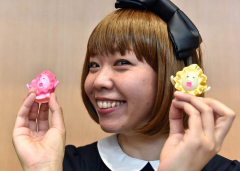 "Japanese artist Megumi Igarashi, who calls herself Rokude Nashiko -- offensive slang which loosely translates as ""reprobate child"" -- shows small mascots shaped to represent a vagina, at a press conference after the first hearing of her trial in Tokyo on April 15, 2015. Igarashi, who has created genital-inspired artworks and was arrested last December on obscenity charges for distributing 3D scans of her own genitals, plead not guilty during the first hearing of her trial at the Tokyo district court. AFP PHOTO / Yoshikazu TSUNO"